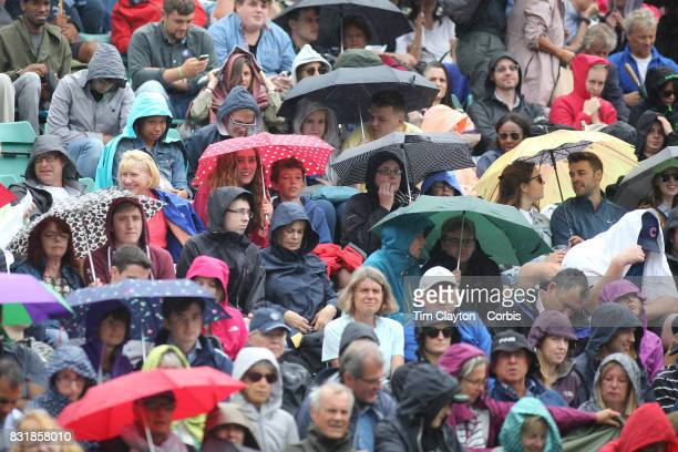 Spectators during a rain delay at the Wimbledon Lawn Tennis Championships held at the All England Lawn Tennis and Croquet Club at Wimbledon on July...