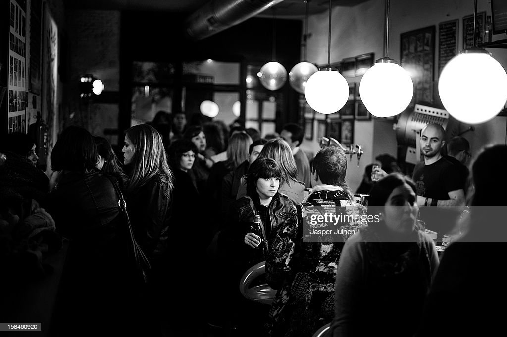 Spectators enjoy a drink in the bar in between the micro theater shows at the 'Micro Teatro por Dinero' on December 15, 2012 in Madrid, Spain. In November 2009, fifty artists presented a theatre project in the thirteen rooms of a former brothel, two weeks before its demolition, with each function lasting less than 10 minutes. The initiative was a huge success, with more people queueing up outside than could enter. Today's 'Micro Theatre For Money' is named after the former brothel on Ballesta Street, and offers a cheap and original way for going out at night, especially in times of financial hardship. With each show priced at 4 Euros, over 150,000 spectators have already attended performances at the tiny theatre in the Malasana area. Anyone can submit a project to be chosen to perform for a month in one of the five tiny rooms in the basement of the theatre, making it an ideal platform for young Spanish authors and actors, often unemployed, to perform. (Photo by Jasper Juinen/Getty Images))