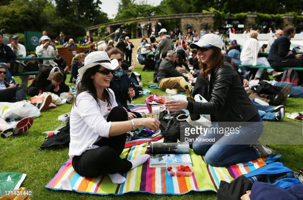 Spectators enjoy strawberries and champagne on Murray Mount as they watch the action on the big screen during day one of the Wimbledon Lawn Tennis...