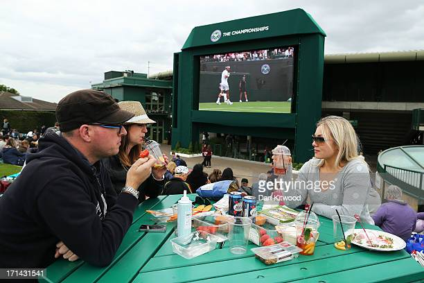 Spectators enjoy strawberries and Pimms on Murray Mount as they watch the action on the big screen during day one of the Wimbledon Lawn Tennis...