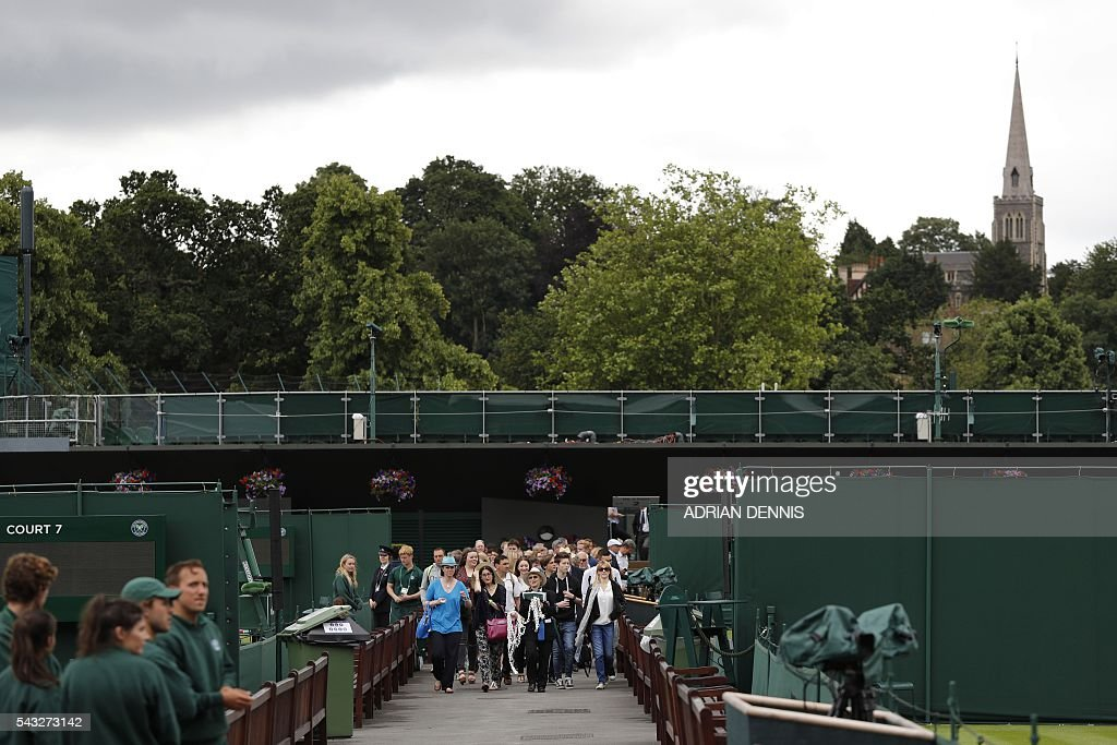 Spectators enter The All England Lawn Tennis Club in Wimbledon, southwest London, on June 27, 2016 on the first day of the 2016 Wimbledon Championships. / AFP / ADRIAN