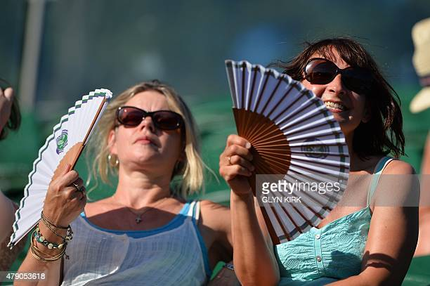 Spectators fan themselves as they watch the action on day two of the 2015 Wimbledon Championships at The All England Tennis Club in Wimbledon...