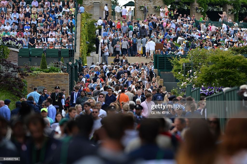 Spectators fill the pavement between the courts at The All England Lawn Tennis Club in Wimbledon, southwest London, on June 27, 2016 on the first day of the 2016 Wimbledon Championships. / AFP / GLYN