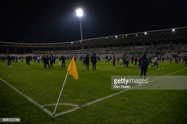Spectators flood the pitch after the referee abandons the match due to repeated pitch invasions during the International Friendly match between the...