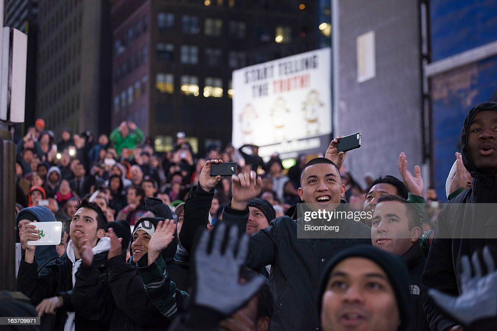 Spectators gather and use their smartphones to document the release of the Samsung Electronics Co. Galaxy S4 smartphone in Times Square in New York, U.S., on Thursday, March 14, 2013. Samsung Electronics Co. unveiled the Galaxy S4 with a bigger screen and software that tracks eye movements as the world's biggest smartphone seller takes its battle with Apple Inc. to the iPhone maker's home market. Photographer: Michael Nagle/Bloomberg via Getty Images