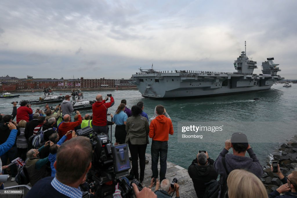 Spectators gather on the dockside as the U.K.'s Royal Navy new aircraft carrier, HMS Queen Elizabeth arrives at its home port in Portsmouth, U.K., on Wednesday, Aug. 16, 2017. The largely French-designed ship will carry 40 aircraft and about 700 crew members was built by a joint venture between BAE Systems Plc, Babcock International Group Plc and Thales SA. Photographer: Luke MacGregor/Bloomberg via Getty Images