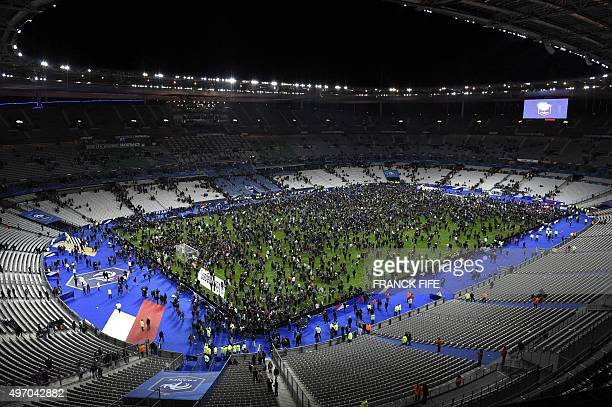 Spectators gather on the pitch of the Stade de France stadium following the friendly football match between France and Germany in SaintDenis north of...