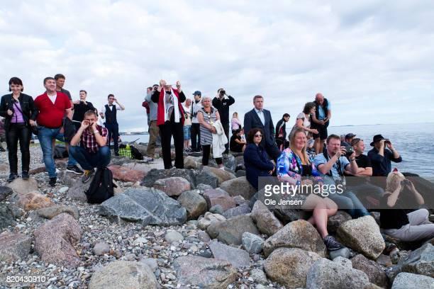 Spectators gather on the shore to watch Russian nuclear submarine 'Dmitrij Donskoj' as it passes the Great Belt Bridge on July 21 2017 near Korsor...