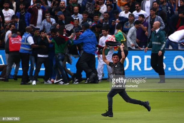 Spectators go wild with excitement as they invade the pitch during the MCC v Afghanistan cricket match at Lord's Cricket Ground on July 11 2017 in...
