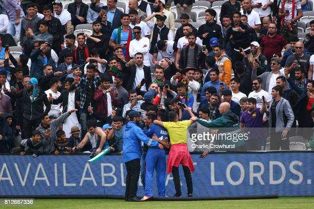 Spectators go wild with excitement as they invade the pitch to get a photo with Rashid Kahn of Afghanistan during the MCC v Afghanistan cricket match...
