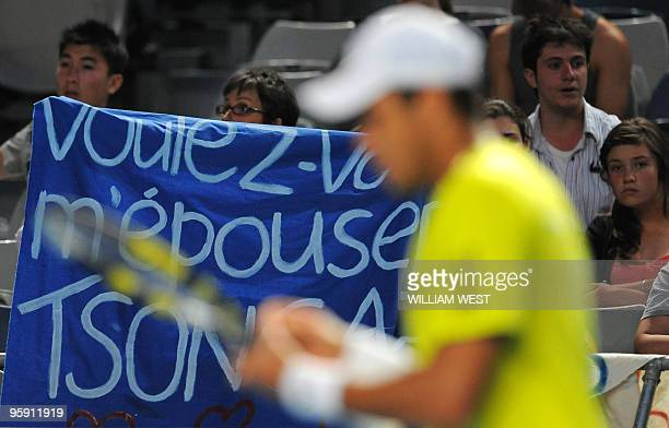 Spectators hold a banner as they cheer for French tennis player JoWilfried Tsonga during his men's singles match against US opponent Taylor Dent on...