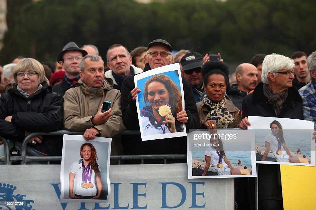 Spectators hold photographs of French swimmer Camille Muffat who died in a helicopter accident while filming French reality TV show 'Dropped' at the...