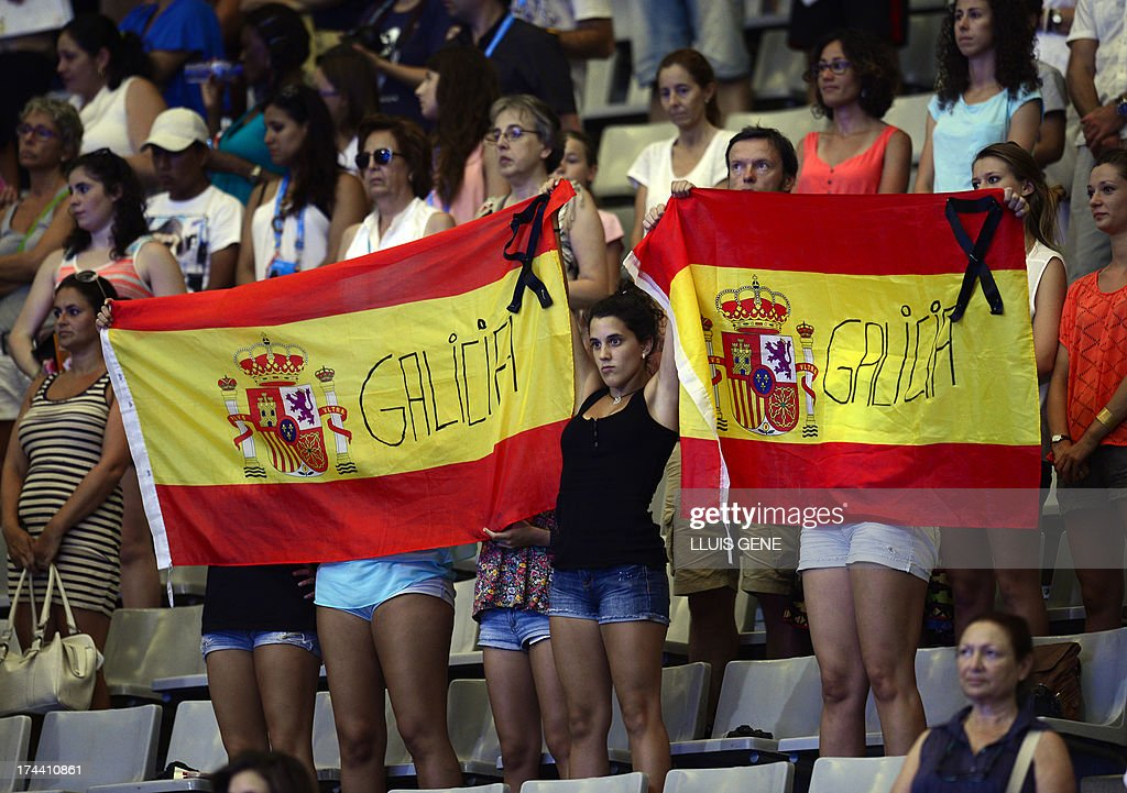 Spectators hold two Spanish national flags as they observe a minute of silence to pay tribute to the victims who died in a train accident prior to the duet free final during the synchronised swimming competition in the FINA World Championships at the Palau Sant Jordi in Barcelona, on July 25, 2013. Spanish police are to grill Thursday the driver of a train that hurtled off the rails at high speed, killing at least 80 passengers in the nation's worst such disaster in decades.