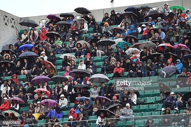 TOPSHOT Spectators hold umbrellas as they watch Japan's Kei Nishikori and Italy's Simone Bolelli during their men's first round match at the Roland...