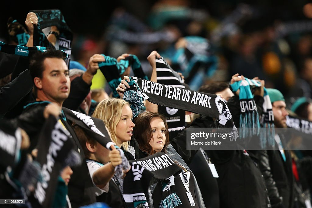 Spectators hold up their scarves during the round 15 AFL match between the Port Adelaide Power and the Richmond Tigers at Adelaide Oval on July 1, 2016 in Adelaide, Australia.