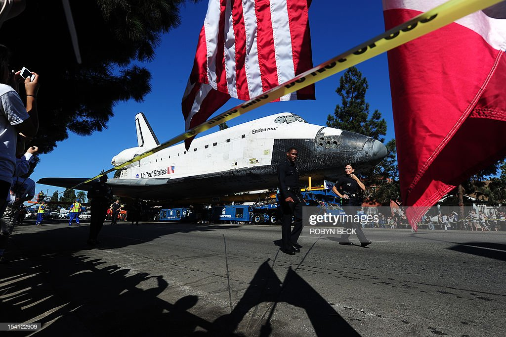 A spectators holds US and Mexican flags as the Space Shuttle Endeavour nears the end of its journey to the California Science Center in Exposition Park in Los Angeles October 14, 2012. The 170,000-pound (77,272 kg) shuttle completed its 12-mile (19km) road trip from Los Angeles International Airport to its permanent museum home just over 18 hours late. AFP PHOTO / Robyn Beck