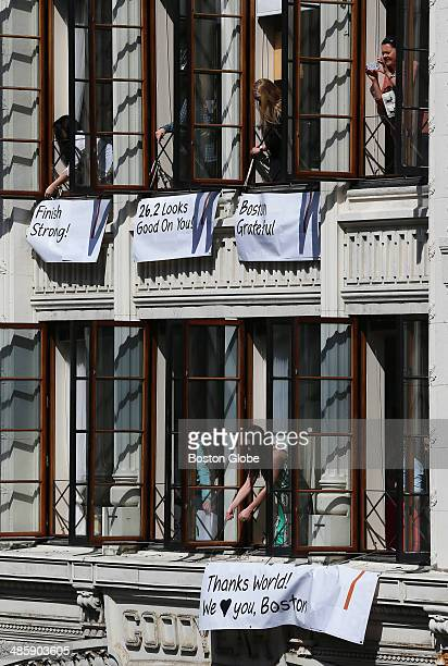 Spectators hung banners with messages like 'Finish Strong' '262 Looks Good On You' 'Boston Grateful' outside windows near the finish line before the...