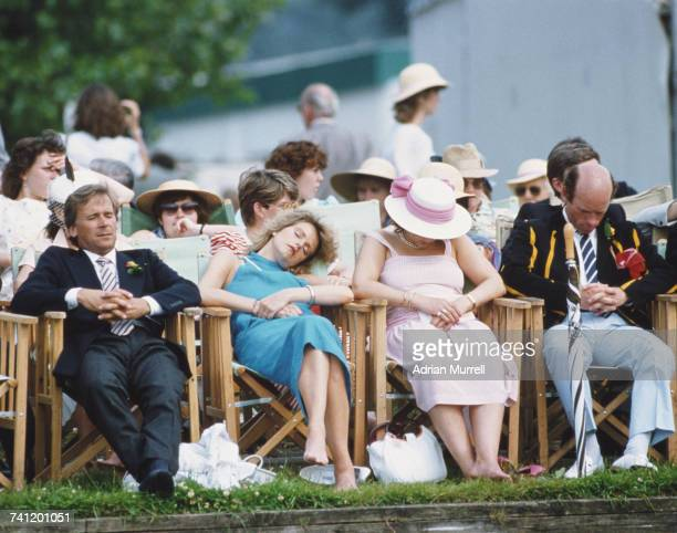 Spectators in the sitting in the Stewards' Enclosure fall asleep in the afternoon sun beside the River Thames whilst watching the rowing at the...