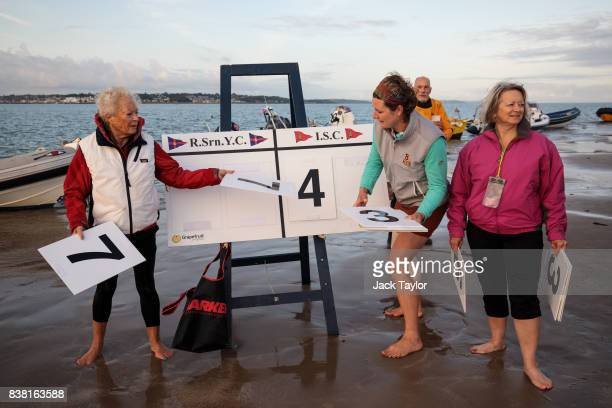 Spectators keep score as teams play a cricket match on the Brambles sandbank at low tide on August 24 2017 in Hamble England The annual event sees...