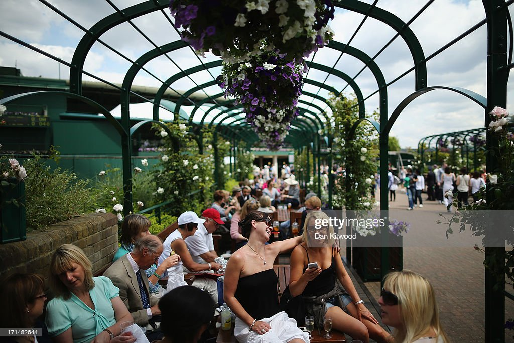 Spectators laugh as they take a break during day two of the Wimbledon Lawn Tennis Championships at the All England Lawn Tennis and Croquet Club on June 25, 2013 in London, England.