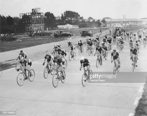 Spectators line the track as the racing cyclists take part in the road race trials for the Cycling World Championships held at the Brooklands motor...