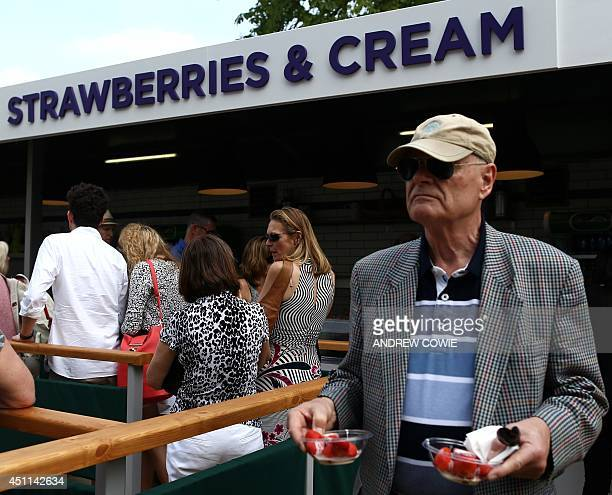 Spectators line up to buy strawberries and cream on day two of the 2014 Wimbledon Championships at The All England Tennis Club in Wimbledon southwest...