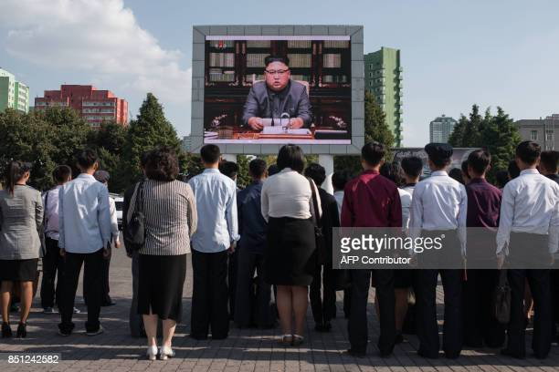 TOPSHOT Spectators listen to a television news brodcast of a statment by North Korean leader Kim JongUn before a public television screen outside the...