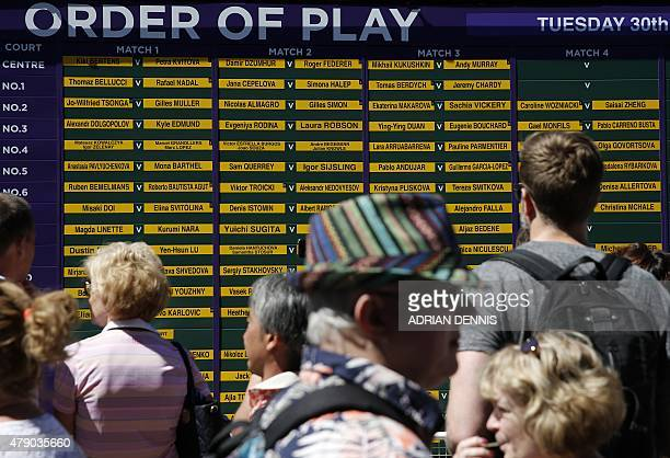 Spectators look at the order of play displayed outside a court on day two of the 2015 Wimbledon Championships at The All England Tennis Club in...