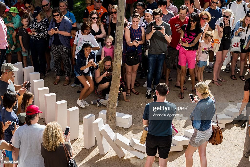 Spectators look on and take photos as large domino pieces collapse during the Arts Centre Melbournes Dominoes arts project in Melbourne, Australia February 6, 2016. More than 7000 giant dominoes snaked through Melbourne city over 2km.