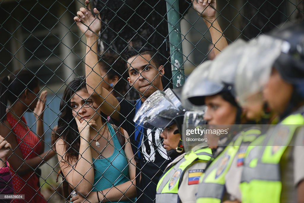 Spectators look on as Bolivarian National Police stand guard near the Central University of Venezuela during pro-opposition students marching near the Central University of Venezuela in Caracas, Venezuela, on Thursday, May 26, 2016. The opposition is pushing for a recall referendum on President Nicolas Maduro and blame the 53-year-old leader for widespread shortages of food and basic necessities. Photographer: Carlos Becerra/Bloomberg via Getty Images