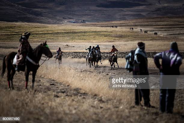 Spectators look on as competitors race through the fields on July 16 2016 in Semonkong Horseracing in the mountain kingdom of Lesotho is not like at...