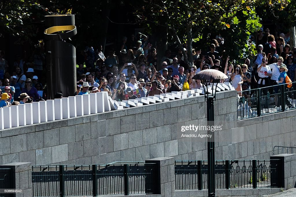 Spectators look on as dominoes collapse during the Arts Centre Melbournes Dominoes arts project in Melbourne, Australia February 6, 2016. More than 7000 giant dominoes snaked through Melbourne city over 2km.