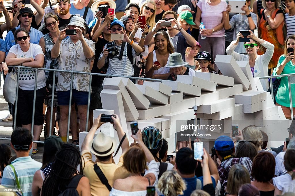 Spectators look on as large domino pieces collapse during the Arts Centre Melbournes Dominoes arts project in Melbourne, Australia February 6, 2016. More than 7000 giant dominoes snaked through Melbourne city over 2km.