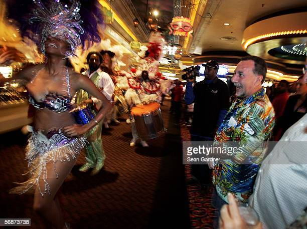 Spectators look on as members of Casa Samba dance through Harrah's Casino while welcoming visitors back during the casino's reopening in New Orleans...