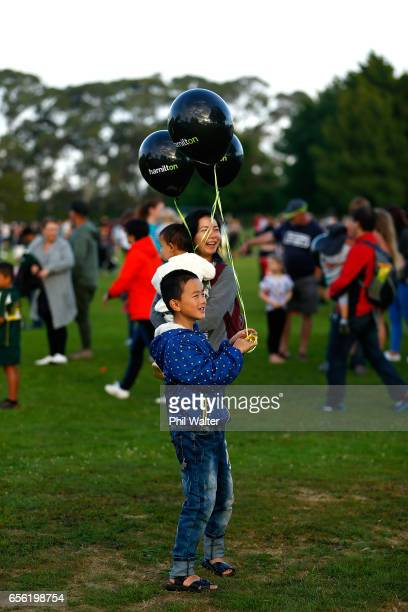 Spectators look on as the hot air balloons begin to take to the air over the Hamilton Lake during the Mass Ascension on the opening day of Balloons...