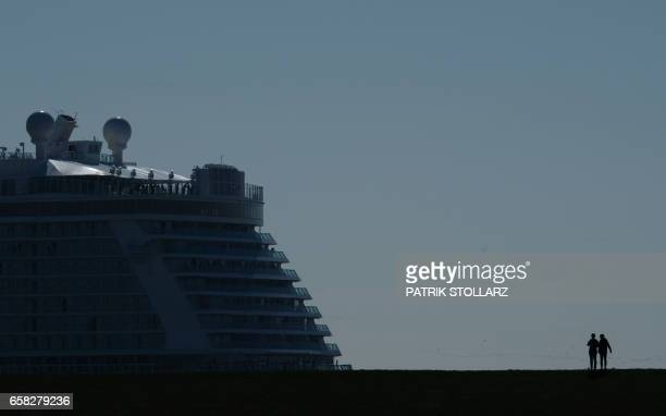 TOPSHOT Spectators look on as the 'Norwegian Joy' cruise ship previously named 'Norwegian Bliss' makes its way over the river Ems near Emden northern...