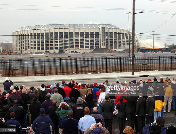 Spectators look on as Veteran's Stadium the former home of the Philadelphia Phillies is imploded to make way for a parking lot March 21 2004 in...