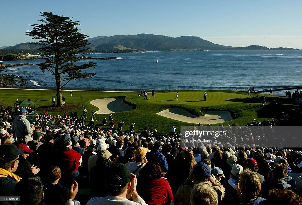 Spectators look on as Vijay Singh of Fiji putts on the 18th green for a threeshot victory at Pebble Beach Golf Links during the ATT Pebble Beach...