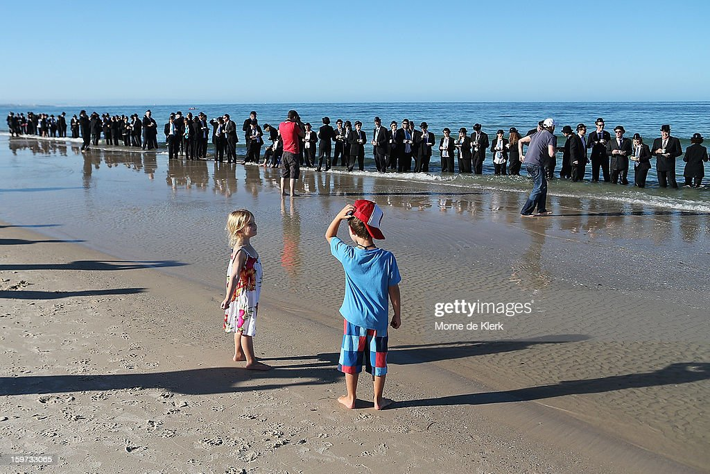 Spectators look on while people stand on the beach in suits and bowler hats as part of an art installation created by surrealist artist Andrew Baines on January 20, 2013 in Adelaide, Australia.