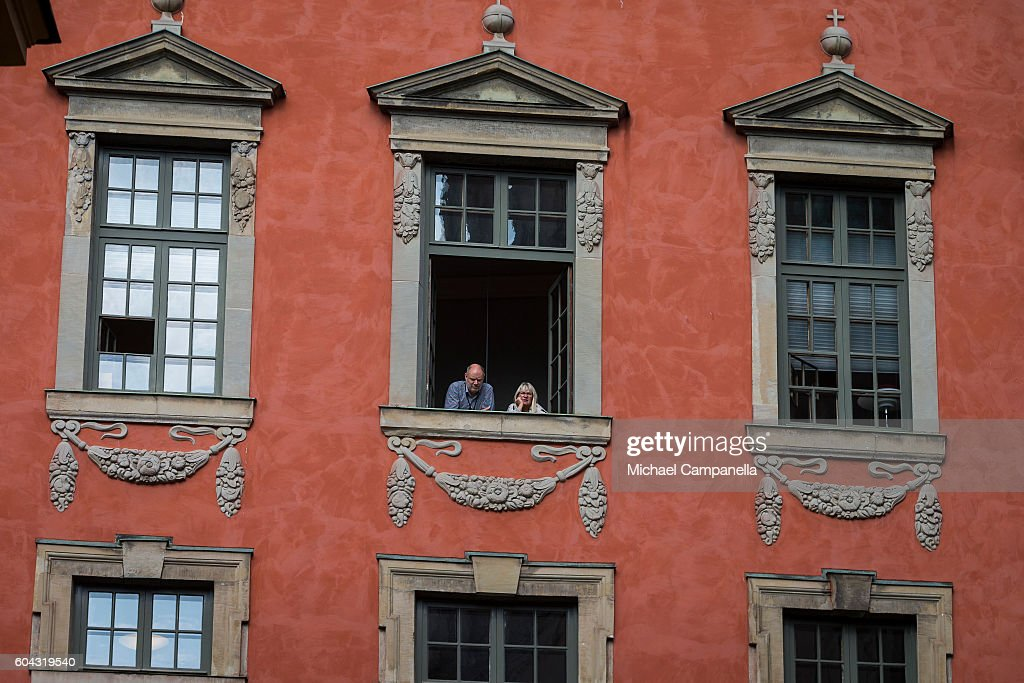 Spectators look out their window and await the arrival of the Swedish king who will attend a ceremony at Storkyrkan in connection with the opening session of the Swedish parliament on September 13, 2016 in Stockholm, Sweden.