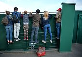 Spectators look over a fence to watch France's Lucas Pouille and Argentina's Juan Martin del Potro during their men's singles third round match on...