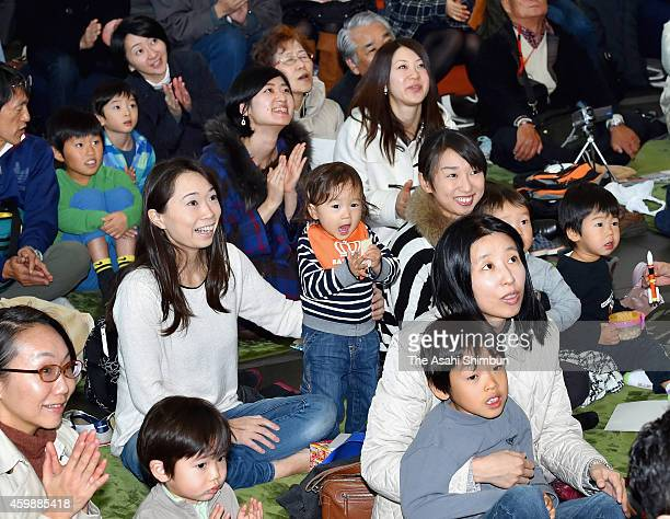 Spectators look up the screen displaying the H2A Launch Vehicle No 26 carrying Hayabusa 2 asteroid probe of Japan Aerospace Exploration Agency...