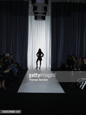 Spectators looking at female model standing on catwalk : Stock Photo