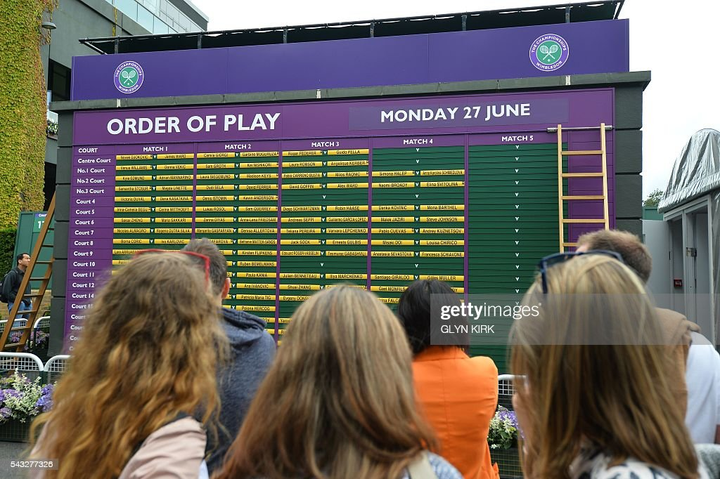 Spectators looks at the order of play at The All England Lawn Tennis Club in Wimbledon, southwest London, on June 27, 2016 on the first day of the 2016 Wimbledon Championships. / AFP / GLYN