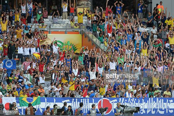 Spectators make the 'wave' as they wait for the start of the FIFA Confederations Cup Brazil 2013 Group A football match between Japan and Mexico at...