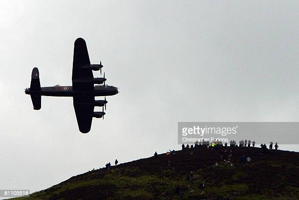 Spectators on a hill look on as a Lancaster bomber flies over Ladybower reservoir in the Derbyshire Peak District to mark the 65th anniversary of the...