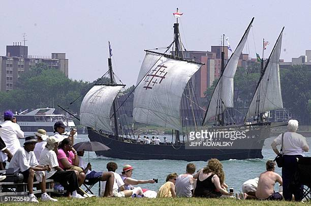 Spectators on Belle Isle in Detroit watch a replica of of Christopher Columbus' Nina as it participates on 22 July in a parade of tall ships down the...
