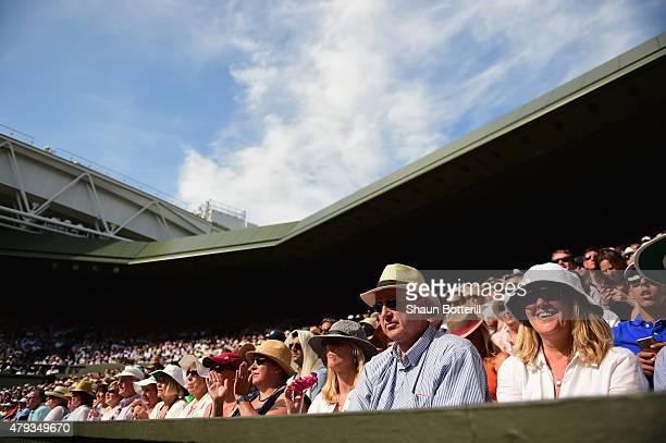 Spectators on Centre Court watch the Gentlemen's Singles Third Round match between Novak Djokovic of Serbia and Bernard Tomic of Australia during day...