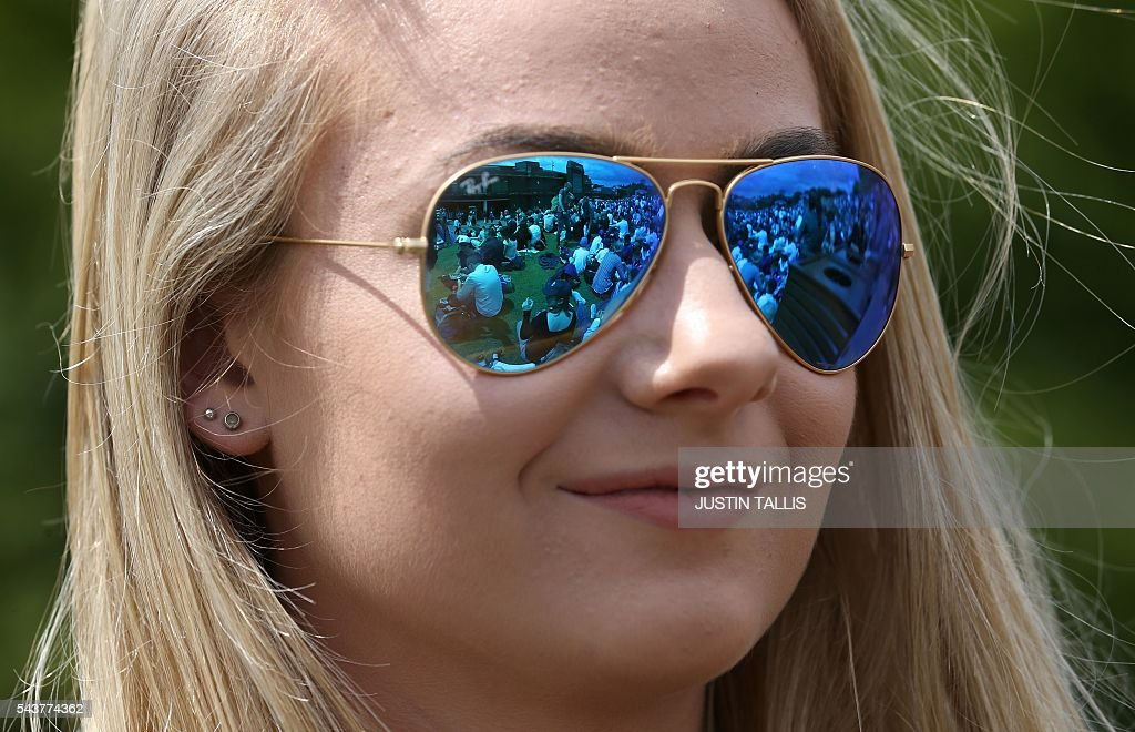 Spectators on Murray mount are reflected in the sunglasses of a tennis fan on the fourth day of the 2016 Wimbledon Championships at The All England Lawn Tennis Club in Wimbledon, southwest London, on June 30, 2016. / AFP / JUSTIN