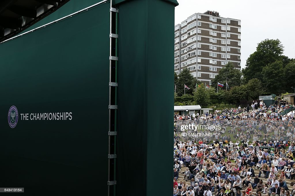 Spectators on Murray Mount (Henman Hill) watch the big screen as Britain's Andy Murray plays against Britain's Liam Broady during their men's singles first round match on the second day of the 2016 Wimbledon Championships at The All England Lawn Tennis Club in Wimbledon, southwest London, on June 28, 2016. / AFP / ADRIAN